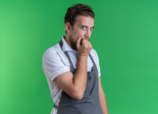 Concerned young male barber wearing uniform bites nails isolated on green wall