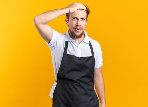 黄色の壁に隔離された額に手を置く制服を着ている心配している若い男性理髪師