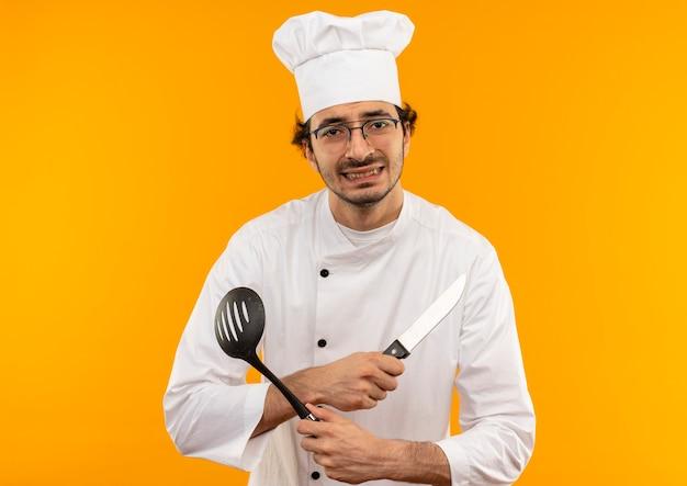 Giovane cuoco maschio interessato che indossa l'uniforme del cuoco unico e vetri che attraversano le mani e che tengono la spatola con il coltello