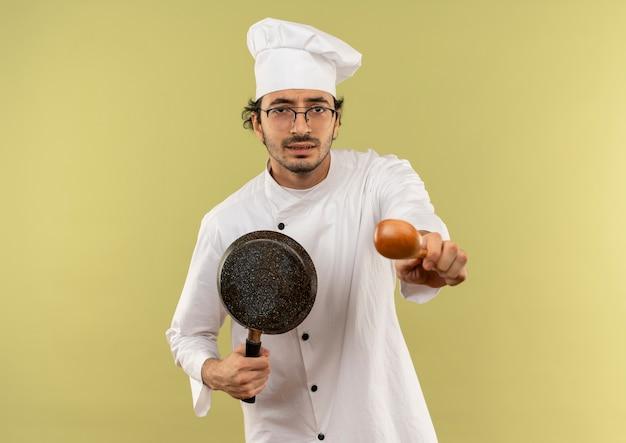 Interessato giovane cuoco maschio che indossa l'uniforme dello chef e bicchieri tenendo la padella e porgendo un cucchiaio