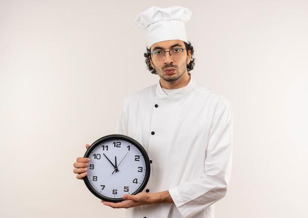 Giovane cuoco maschio interessato che indossa l'uniforme del cuoco unico e vetri che tengono l'orologio di parete