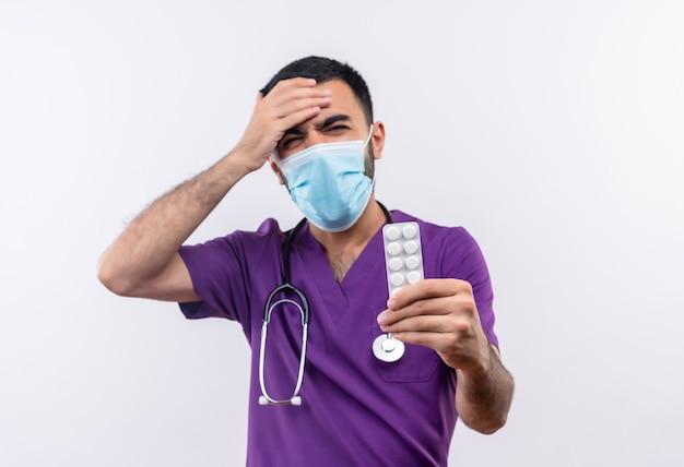 Обеспокоенный молодой мужчина-врач в фиолетовой одежде хирурга и в медицинской маске со стетоскопом, держащий таблетки, положил руку на лоб на изолированную белую стену