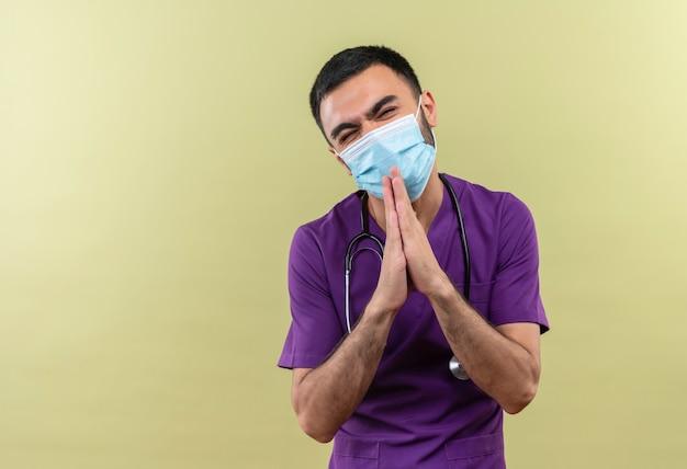 紫色の外科医の服と聴診器の医療マスクを身に着けている心配している若い男性医師は、孤立した緑の壁に祈りのジェスチャーを示しています
