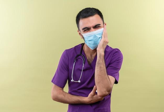 Il giovane medico maschio interessato che indossa l'abbigliamento viola del chirurgo e la mascherina medica dello stetoscopio ha messo la sua mano sulla guancia sulla parete verde isolata