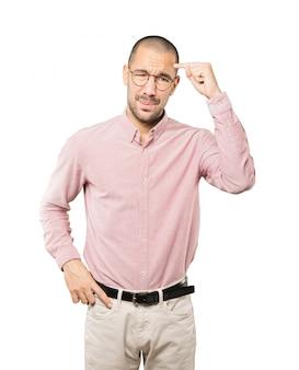 Обеспокоенный молодой человек делает жест растерянности