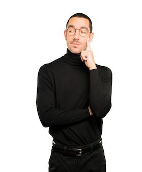 Обеспокоенный молодой человек делает жест сомнения