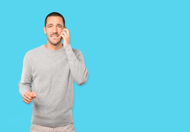 Обеспокоенный молодой человек, царапающий жест