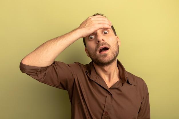 Giovane preoccupato che mette la mano sulla fronte che esamina la parte anteriore isolata sulla parete verde oliva