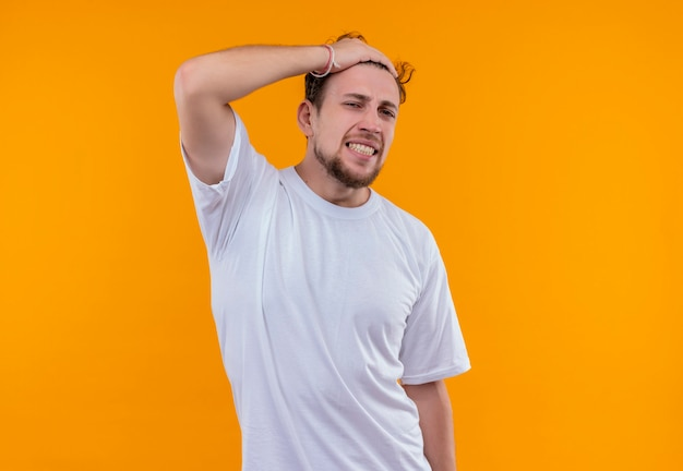 白いtシャツを着ている心配している若い男は、孤立したオレンジ色の壁に頭に手を置いた