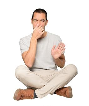 嫌悪感のジェスチャーで心配している若い男