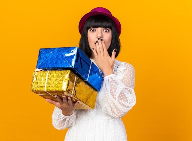 コピースペースでオレンジ色の壁に隔離された口に手を保つギフトパッケージを保持しているパーティーハットを身に着けている心配している若いパーティーの女の子