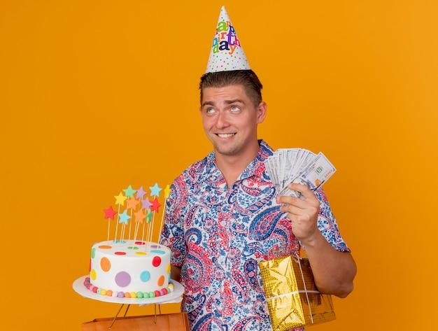 オレンジ色に分離された贈り物と現金でケーキを保持している誕生日の帽子をかぶって見上げる心配している若いパーティーの男