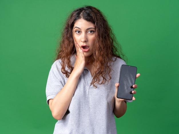 휴대 전화를 보여주는 얼굴에 손을 유지 걱정 젊은 예쁜 백인 여자