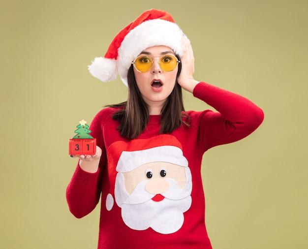 Обеспокоенная молодая симпатичная кавказская девушка в свитере санта-клауса и повязке на голову в очках держит елочную игрушку с датой