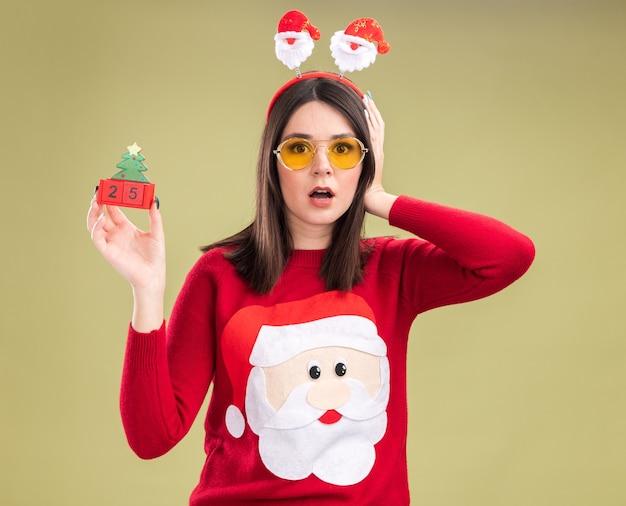 Giovane ragazza graziosa caucasica interessata che indossa il maglione e la fascia del babbo natale con gli occhiali che tengono il giocattolo dell'albero di natale con la data
