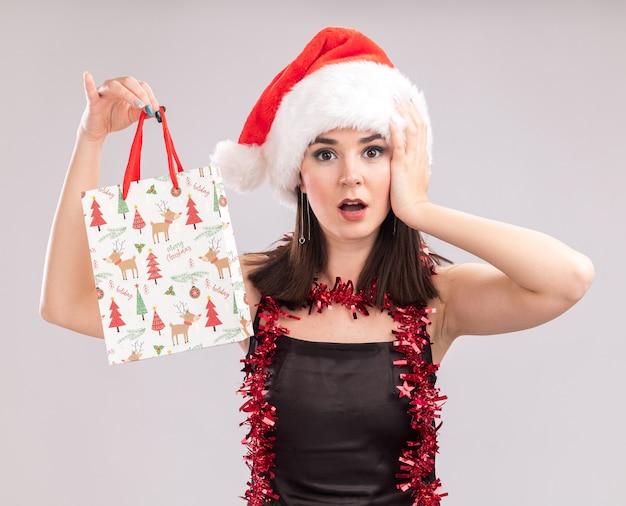 Обеспокоенная молодая симпатичная кавказская девушка в шляпе санта-клауса и гирлянде из мишуры на шее, держащая рождественский подарочный пакет, смотрит в камеру, держа руку на голове, изолированную на белом фоне