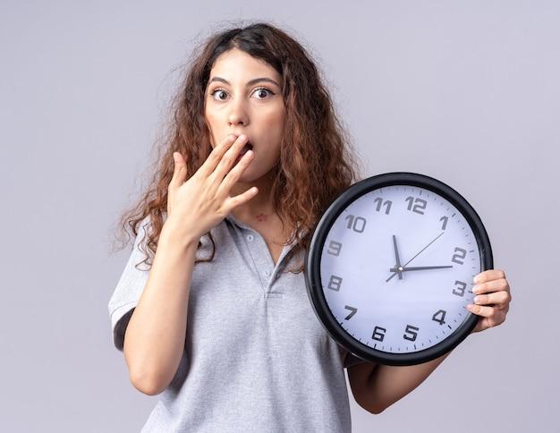 Preoccupato per la giovane donna piuttosto caucasica che tiene l'orologio tenendo la mano sulla bocca