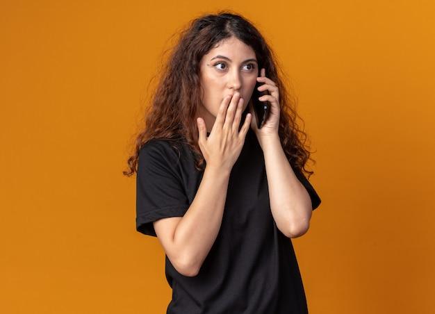 복사 공간이 있는 주황색 벽에 격리된 면을 바라보며 입에 손을 대고 전화 통화를 하는 걱정스러운 어린 소녀