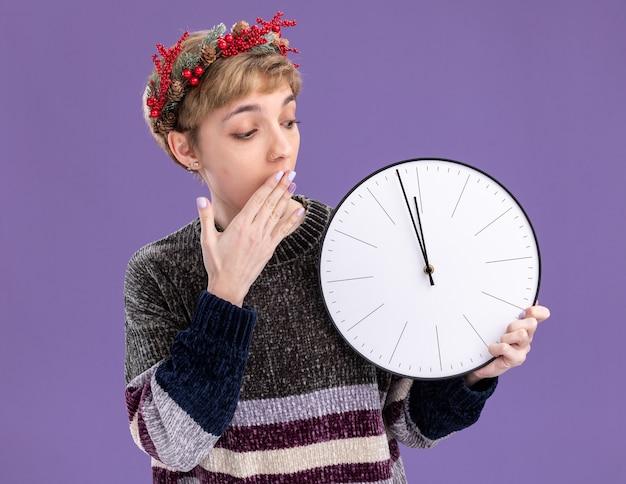 Giovane ragazza graziosa interessata che indossa la corona della testa di natale che tiene e che guarda l'orologio che tiene la mano sulla bocca isolata su fondo viola
