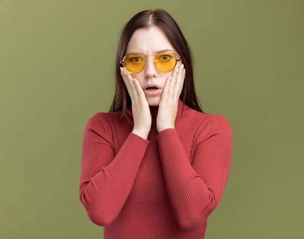 Concerned young pretty girl wearing sunglasses keeping hands on face