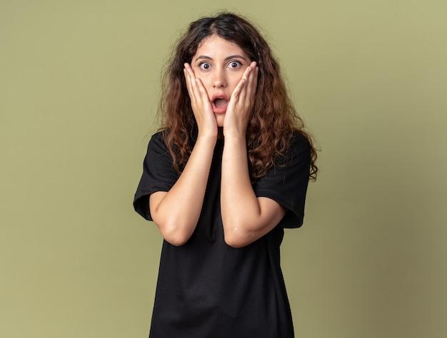 Обеспокоенная молодая красивая женщина смотрит на фронт, держа руки на лице, изолированном на оливково-зеленой стене с копией пространства