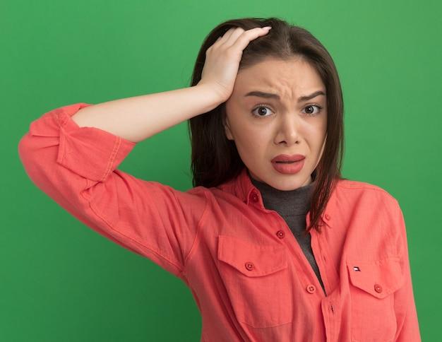 Preoccupato per la giovane donna graziosa che mette la mano sulla testa guardando la parte anteriore isolata sul muro verde