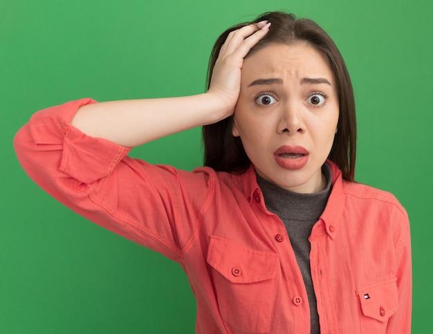 緑の壁に隔離された正面を見て頭に手を置く心配若いきれいな女性