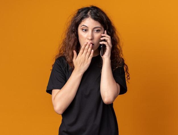 Обеспокоенная молодая красивая женщина разговаривает по телефону, держась за рот, глядя в сторону