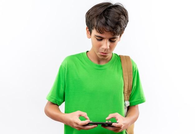 Il giovane ragazzo di scuola interessato che indossa lo zaino gioca sul telefono isolato sul muro bianco