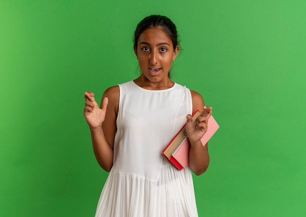 Giovane scolara interessata che tiene libro con il taccuino e le dita incrociate