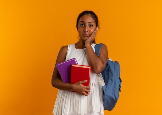 Zaino da portare della giovane scolara interessata che tiene i libri e che mette la mano sulla guancia