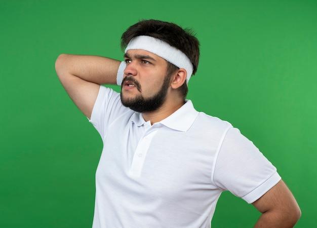 Giovane uomo sportivo interessato che esamina la fascia e il braccialetto da portare laterali che mettono la mano sul collo isolato sul verde