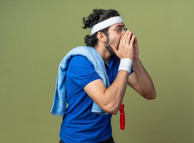 Обеспокоенный молодой спортивный мужчина в повязке на голову с браслетом и полотенцем со скакалкой на плече зовет кого-то