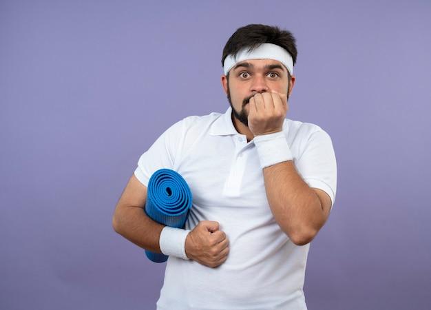 Interessato giovane sportivo da indossare fascia e braccialetto che tiene la stuoia di yoga mettendo la mano sulla bocca isolata sulla parete verde con lo spazio della copia