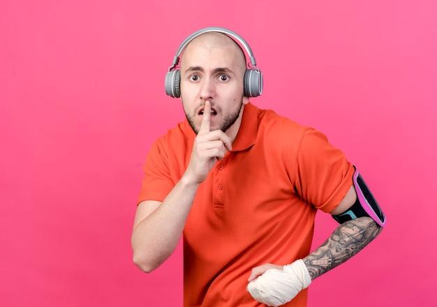 ピンクの壁に分離された沈黙のジェスチャーを示す電話の腕章とヘッドフォンを身に着けている手首の包帯を持つ心配している若いスポーティな男
