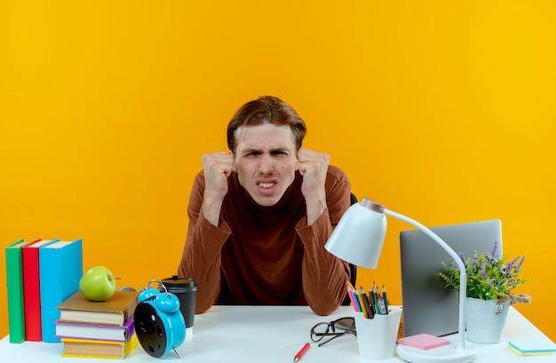 Ragazzo giovane studente interessato che si siede allo scrittorio con gli strumenti della scuola che mostrano sì gesto