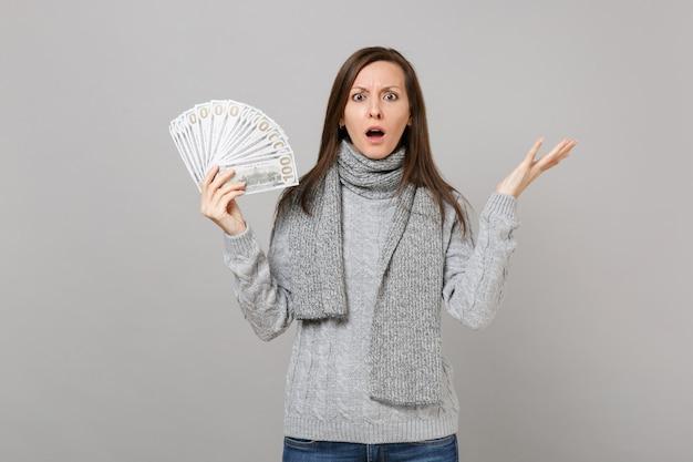 Обеспокоенная молодая женщина в сером шарфе свитера, раздвигая руки, держит много кучу долларов, банкноты, наличные деньги, изолированные на сером фоне. эмоции людей здорового образа жизни моды, концепция холодного сезона.