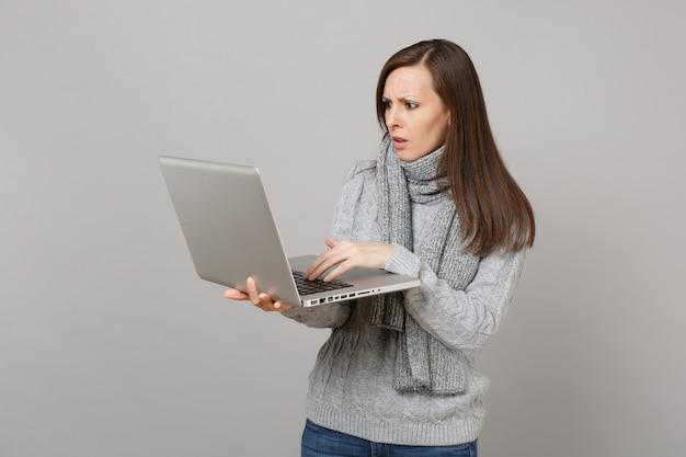 灰色のセーター、灰色の壁の背景で隔離のラップトップpcコンピューターで作業しているスカーフで心配している若い女性。健康的なライフスタイル、オンライン治療コンサルティング、寒い季節のコンセプト。コピースペースをモックアップします。