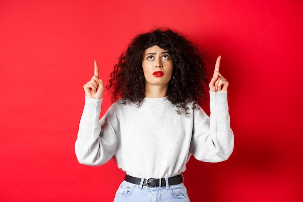 Обеспокоенная молодая женщина с вьющимися волосами, хмурящаяся и сомневающаяся, указывая вверх с нерешительным или встревоженным лицом, стоя на красном фоне.