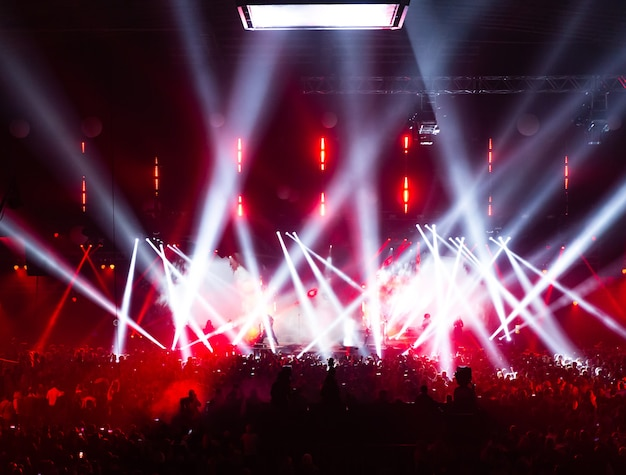 Концертная толпа веселится на рок-концерте. большой концертный зал с большой сценой. много людей. осветительное оборудование.