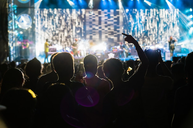 Concert crowd in silhouettes of music fanclub with show hand action which follow up the songer at the front of stage with follow light, musical and concert concept