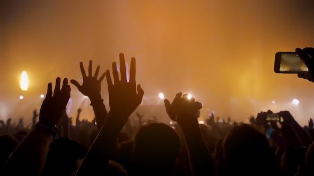 콘서트 음악 축제 및 축하. 파티 사람들 록 콘서트. 행복하고 즐겁고 박수 또는 박수 군중. 흐릿한 나이트 클럽. 무대에서 dj 뮤직 페스티벌 edm과 함께 콘서트 쇼