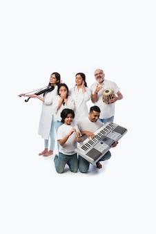 Концерт индийской семьи из шести человек, играющих на музыкальных инструментах в группе, и старшая дама, поющая, стоя на белом фоне