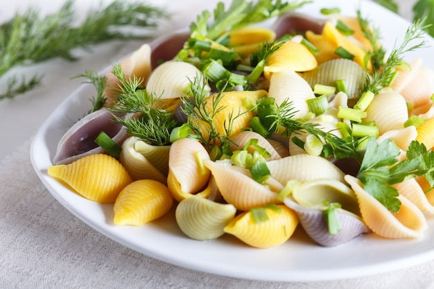 Conchiglie colored pasta with fresh greengrocery on a linen tablecloth