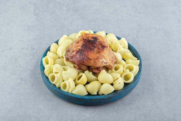 Паста конкильи и курица-гриль на синей тарелке.