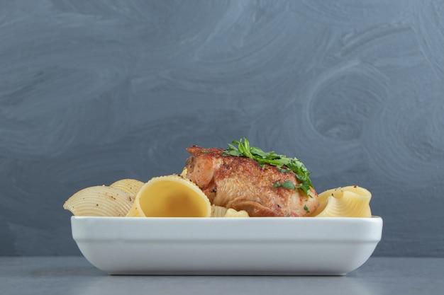 Макаронные изделия conchiglie и жареный цыпленок на белой тарелке.