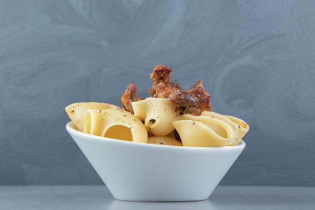 Conchiglie con pollo alla griglia in ciotola bianca