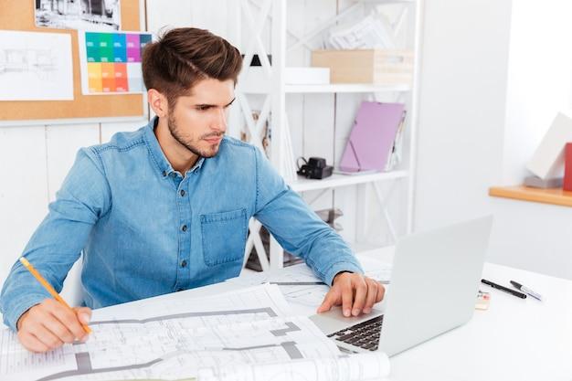 Концентрированный молодой бизнесмен с документами и ноутбуком, сидя в офисе