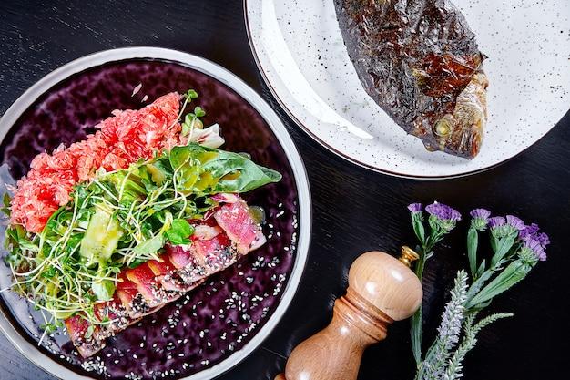 ランチのシーフードテーブルのフラットレイアウト。マグロのグレープフルーツとグリーンサラダのグリル、魚のドラドのグリル。健康的なダイエット食品のconcpet。ランチを提供するレストラン。シーフードサラダ