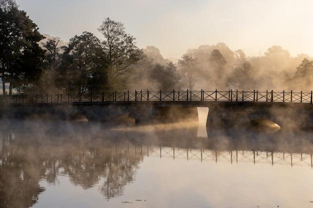안개로 덮여 나무로 둘러싸인 호수 위에 콘크리트 아치 다리